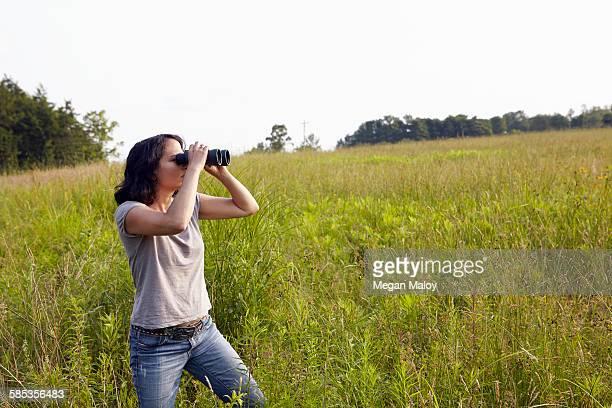 Woman looking through binoculars from field of long grass