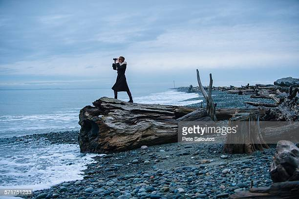 Woman looking through binoculars from large driftwood tree stump on beach