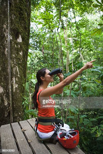 Woman looking through binoculars in forest, Islas del Rosario, Colombia