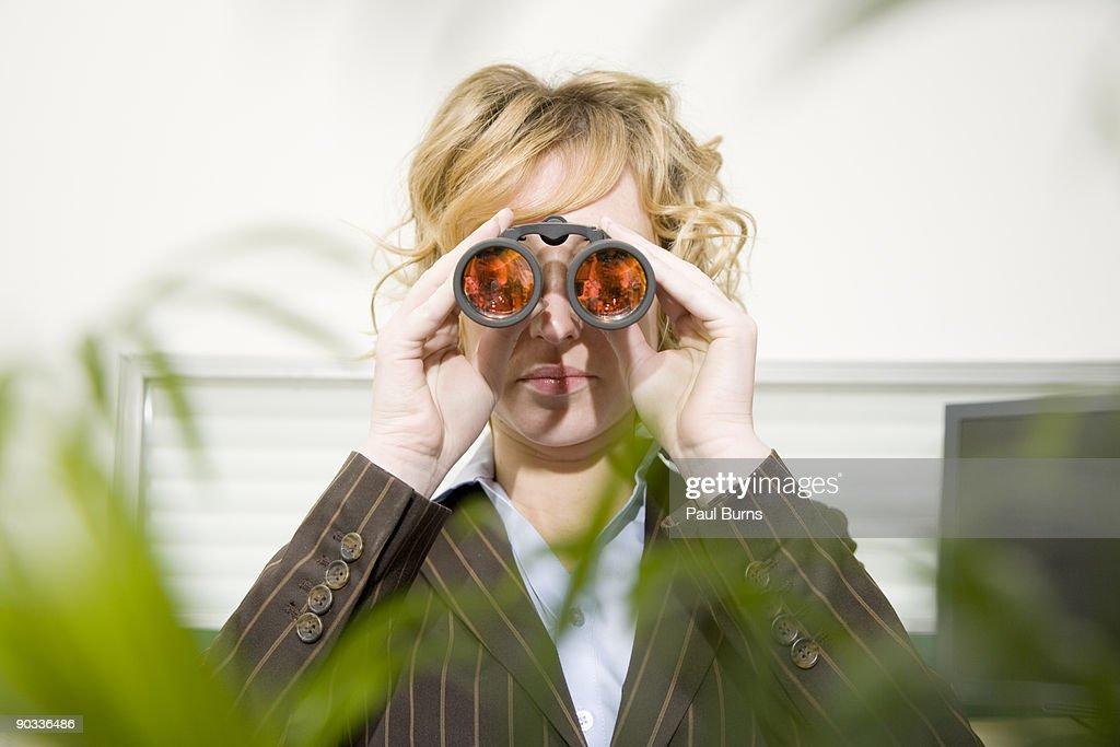 Woman Looking Through Binoculars in Office : Stock Photo