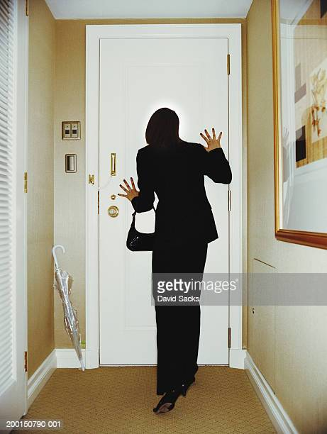 Woman looking through door peephole, rear view