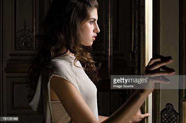 Femme en train de regarder par la porte