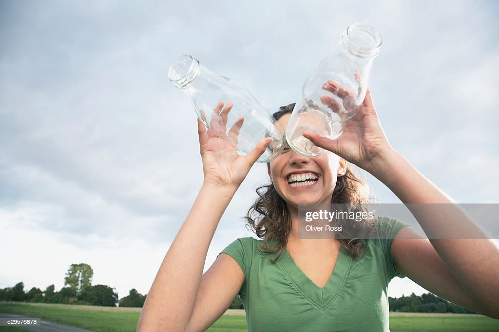 Woman Looking Through Glass Bottles : Stock-Foto