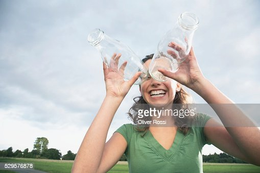 Woman Looking Through Glass Bottles : Photo