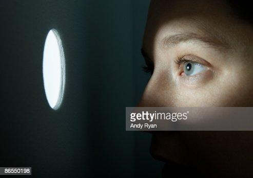 Woman looking through illuminated peep hole. : Stock Photo