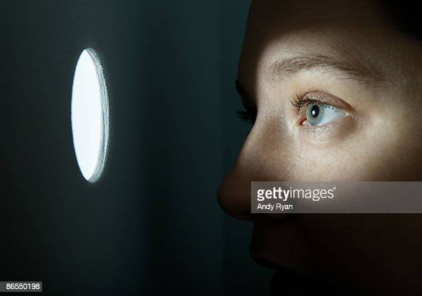 Woman looking through illuminated peep hole.