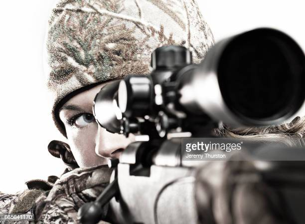 Woman looking through scope on rifle wearing camouflage