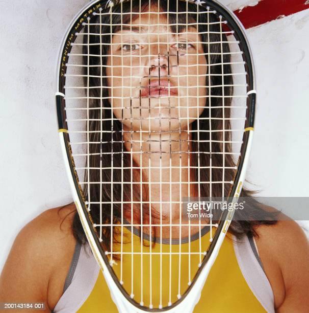 Woman looking through squash racquet, portrait