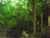 Woman looking through stone archway in jungle