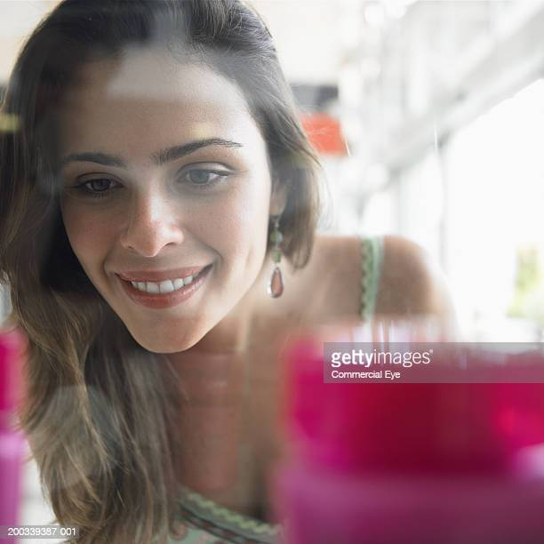 Woman looking through store window display, close-up