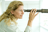 Woman looking through telescope, smiling, profile