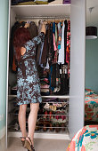 Woman looking through wardrobe, rear view