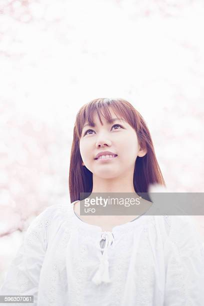 Woman looking up at cherry blossoms