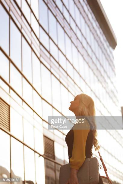 Woman looking up at mirrored city building