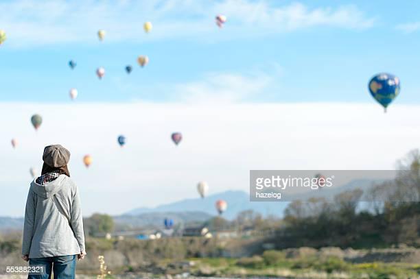 Woman looking up at the hot air balloons