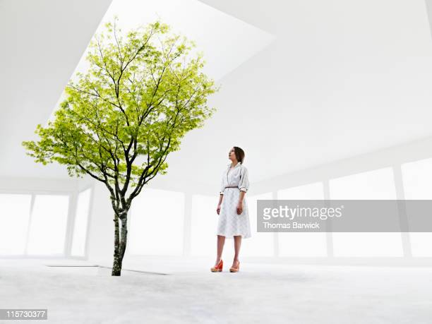Woman looking up at tree growing out of stairwell