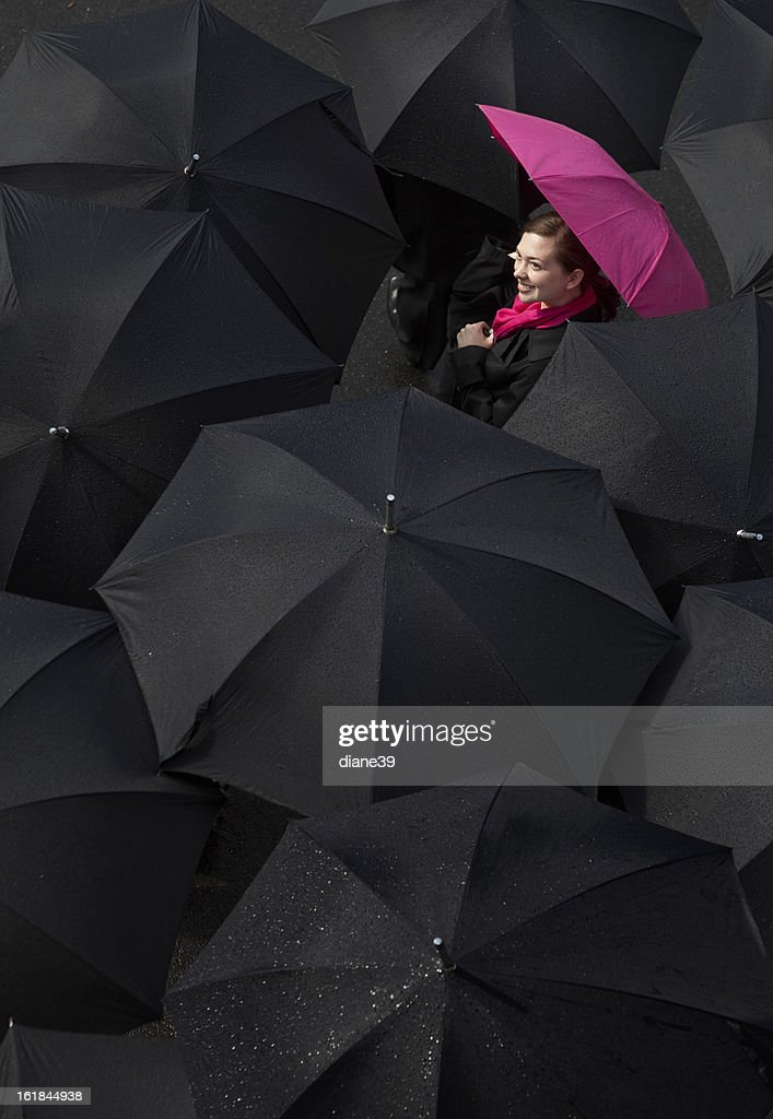 Woman looking up from under an umbrella : Stock Photo