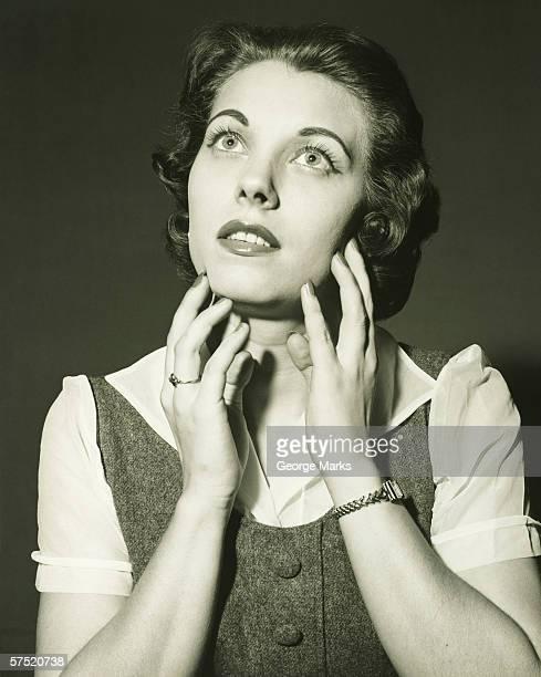Woman looking up in studio, (B&W), portrait