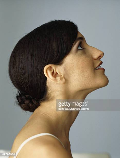 Woman looking up, smiling, profile