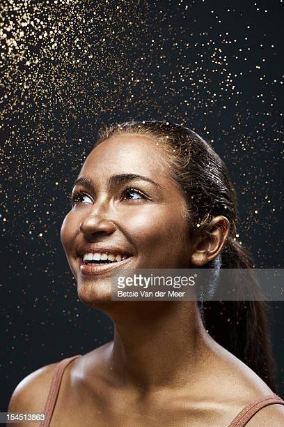 Woman looking up to rain of sparkles,laughing.