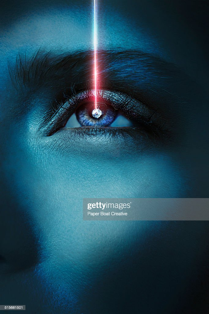 woman looking up while a laser beam hits her eye