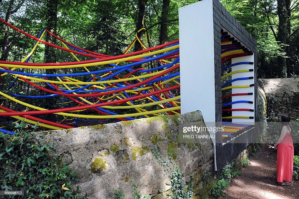 A woman looks at a 3D abstract painting by the French-Serbian artist Igor Antic intitled 'Allochtone', in Mellionnec, western France, on June 13, 2014, as part of the 'Lieux mouvants' ('Moving Places') art event where contemporary art meets nature, by blending in gardens and sacred places.