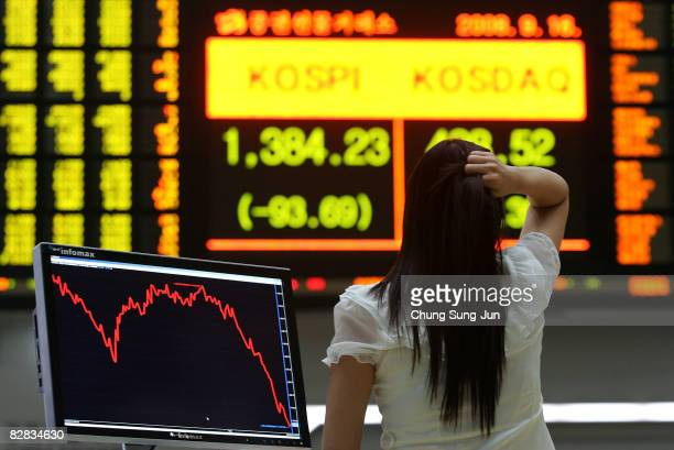 A woman looks at a board showing stock price index at a stock brokerage firm on September 16 2008 in Seoul South Korea The Korean stock markets has...