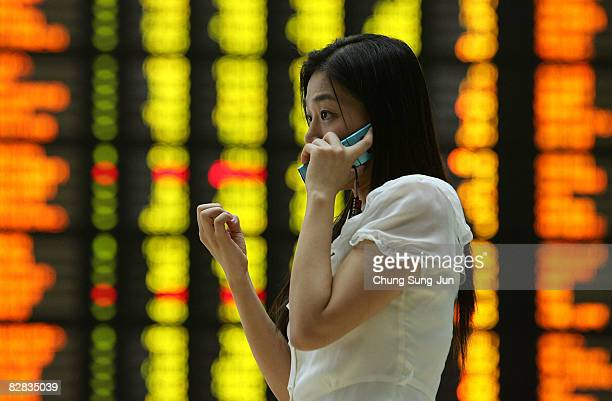 A woman looks at a board showing stock price index at a stock brokerage firm in Seoul September 16 2008 in Seoul South Korea The Korean stock markets...