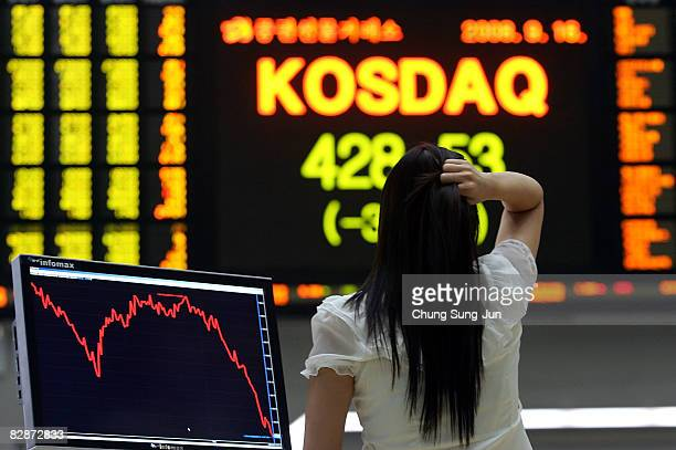 A woman looks at a board showing stock price index at a stock brokerage firm on September 16 2008 in Seoul South Korea The Korean Won has plummeted...