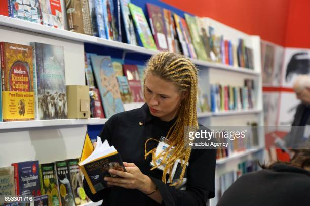 A woman looks at a book at the Olympia Fair Center during the 46th London Book Fair the global marketplace for rights negotiation and the sale and...