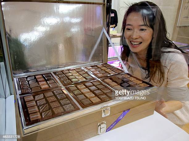 A woman looks at a box of chocolates produced by Jean Paul Hevin and priced at 37032 yen as a gift for Valentine's Day at Tokyo's Mitsukoshi...