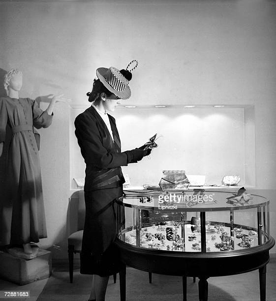 A woman looks at a butterfly brooch by French fashion designer Jeanne Lanvin as she stands next to a case of other jewellery at the designer's shop...