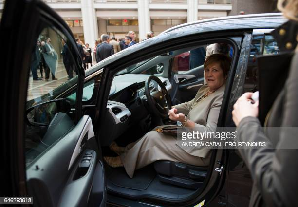 A woman looks at a Chevrolet Bolt before attending a winter luncheon with Mary T Barra Chairman and CEO of General Motors Company in Washington DC on...