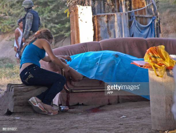 A woman looks at a corpse lying on a sofa on December 18 2008 in Culiacan Sinaloa state Mexico In Mexico where on a daily basis the drug trafficking...
