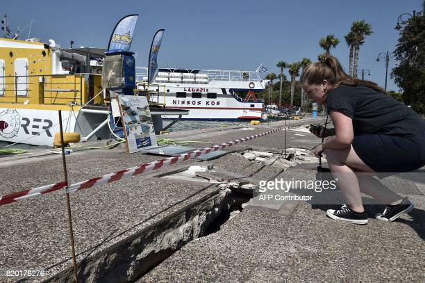 A woman looks at a crack at the Kos harbour following a 65 magnitude earthquake which struck the region on July 21 2017 Two foreigners died and more...
