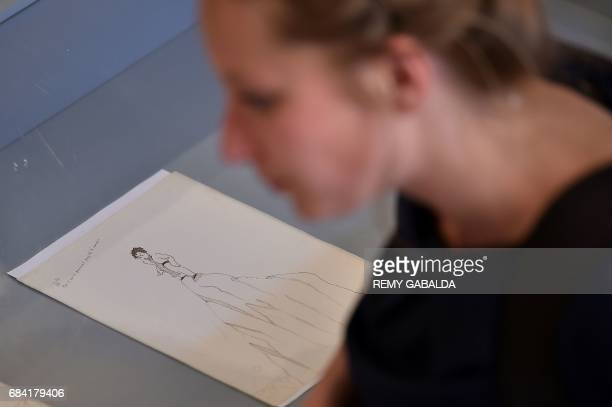 A woman looks at a drawing by French man Antoine de SaintExupéry is shown at the Museum of Old Toulouse on May 17 prior to the set of 12 drawings and...