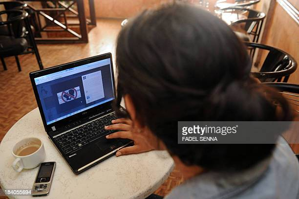 A woman looks at a Facebook page in Agadir on October 11 published in support of the three Moroccan teenagers arrested for posting Facebook photos of...