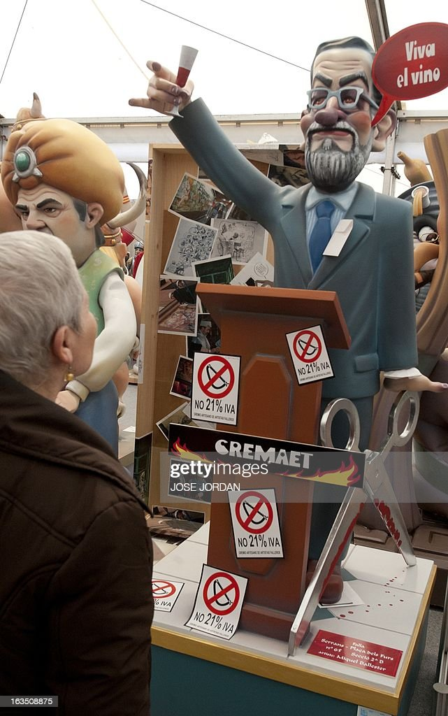 A woman looks at a Falla, a gigantic sculpted structure of cardboard and wood which humorously portrays relevant current events and personalities, caricaturing Spain's Prime Minister Mariano Rajoy, during an exhibition before preparations for the Fallas Festival, in Valencia on March 11, 2013. The Fallas will be burned in the streets of Valencia on March 19, 2013, as a tribute to St. Joseph, patron saint of the carpenters' guild.
