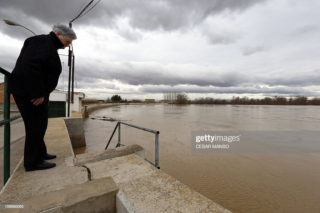 A woman looks at a flooded area following the rise of the River Ebro, due to heavy rainfall, in Cabanas de Ebro near Zaragoza, on January 22, 2013.
