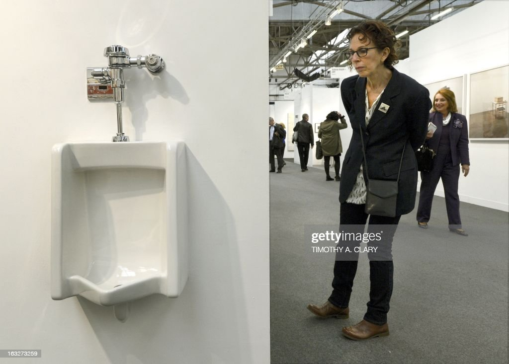 A woman looks at a fully functional urinal by artist Andrew Ohanesian title 'Urinal' during the press preview at the 2013 Armory Show, one of the world's top art events featuring the most influential artworks of the 20th and 21st centuries, at Pier 92 and 94 in New York March 6, 2013. The Armory Show Centennial Edition kicks off Armory Arts Week .
