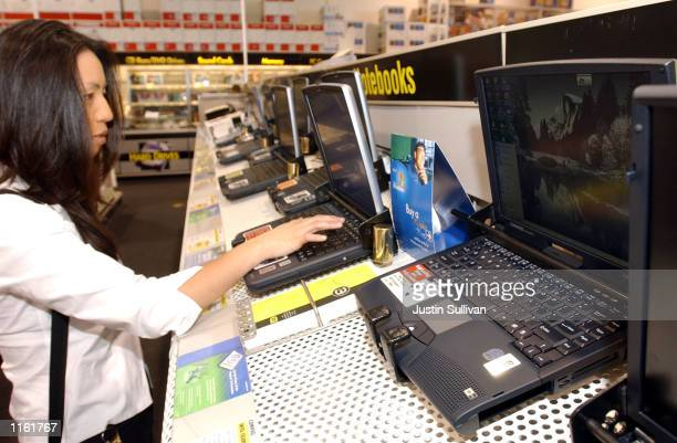 A woman looks at a Hewlett Packard laptop that is next to a Compaq laptop at Best Buy electronics store September 5 2001 in San Carlos California...