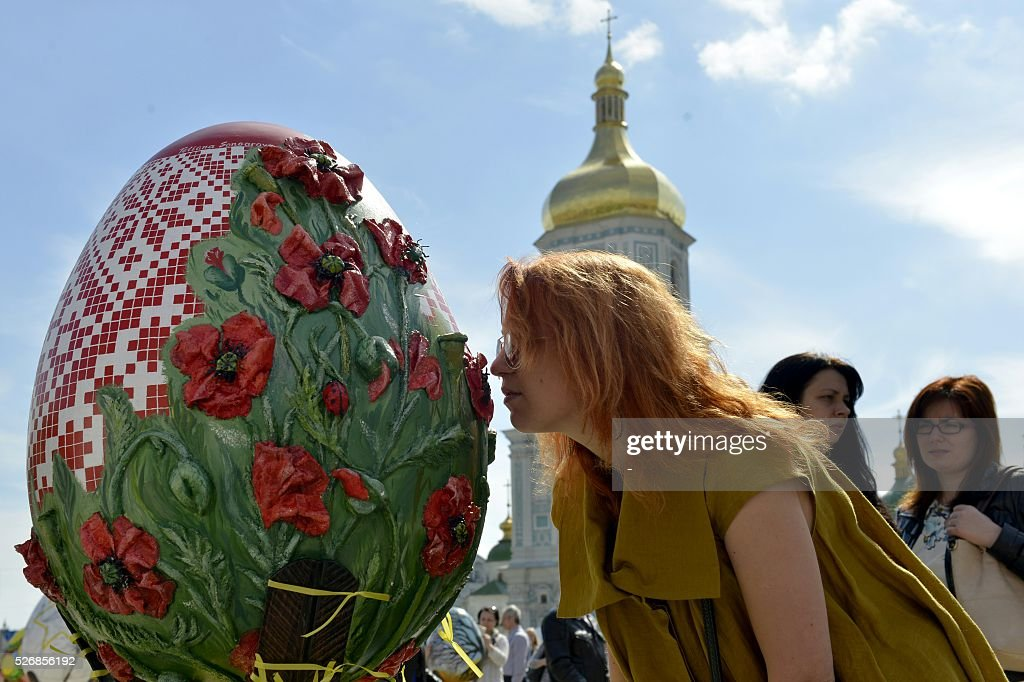 A woman looks at a huge 'Pysanka', a traditional Easter egg, during the celebrations of Orthodox Easter as part of the Pysanka festival in Kiev on May 1, 2016. 374 huge eggs and 40 000 small ones decorated by Ukrainian artists are displayed at St. Sophiya square in Kiev. / AFP / -