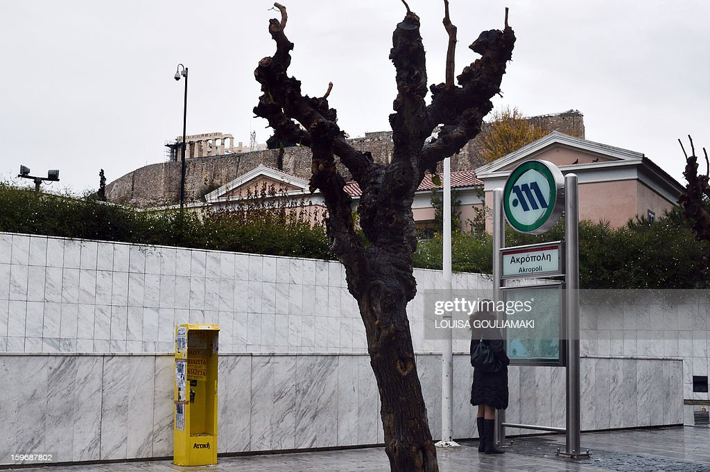 A woman looks at a map by a closed subway station in Athens due to a 24-hours emloyees strike on January 18, 2013. Athens metro, tram and urban railway workers walked off the job to protest salary cuts as part of the new round of austerity measures.
