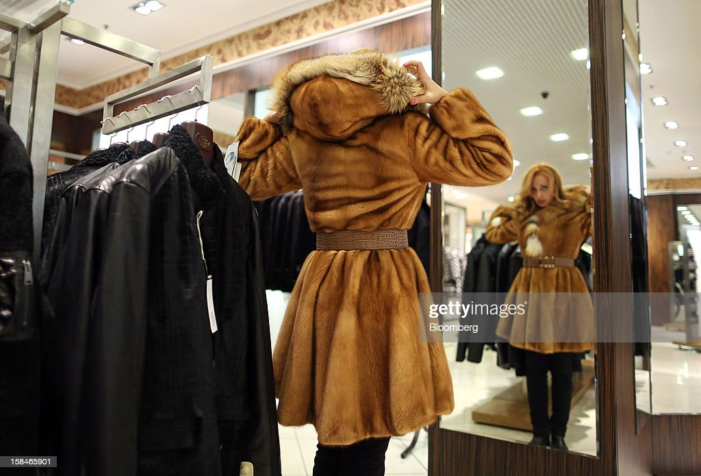 A woman looks at a mirror while trying on a Mink fur coat in this arranged photograph at the World of Fur and Leather store in Moscow, Russia, on Sunday, Dec. 16, 2012. Russia's government should introduce a tax on luxury consumption in first half of 2013, President Vladimir Putin said in state-of-the-nation address in Moscow. Photographer: Andrey Rudakov/Bloomberg via Getty Images