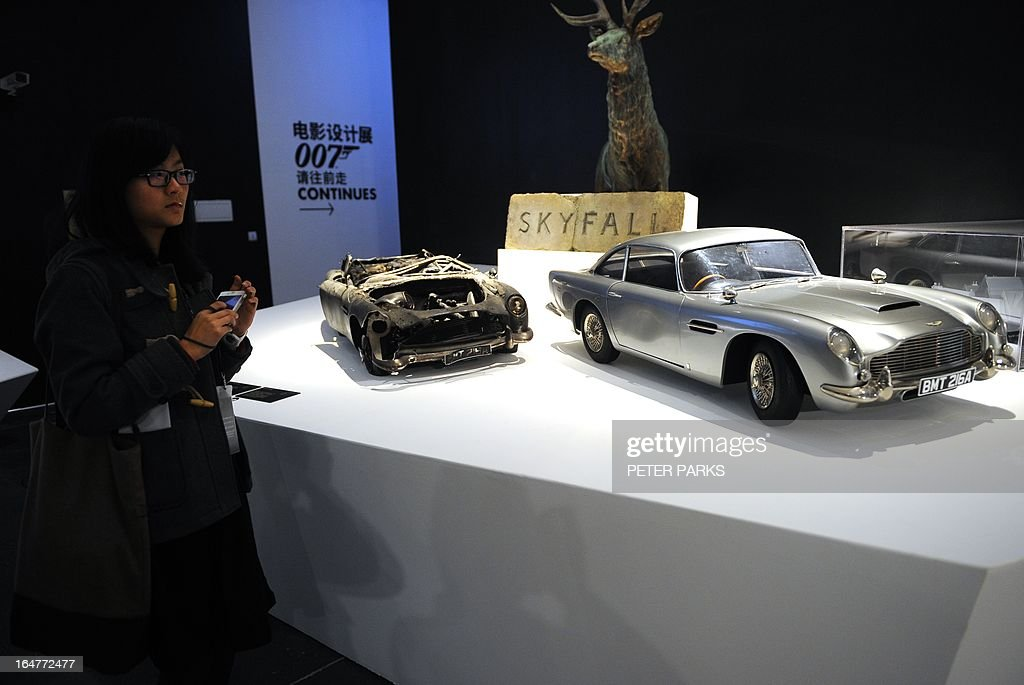 A woman looks at a model of James Bond's Aston Martin DB5 and other props from the movie'Skyfall' at an exhibition on the fictional British spy in Shanghai on March 28, 2013. The exhibition opened in Shanghai just weeks after the Communist government's censors cut parts of the latest film in the franchise, 'Skyfall' with a scene showing prostitution in Macau, a special administrative region of China, was removed, as was a line in which Bond's nemesis mentions being tortured by Chinese security agents. AFP PHOTO/Peter PARKS