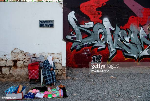 A woman looks at a mural as she sells items on the street during the 'Jidar' street art Festival in the capital Rabat on April 20 2017 / AFP PHOTO /...