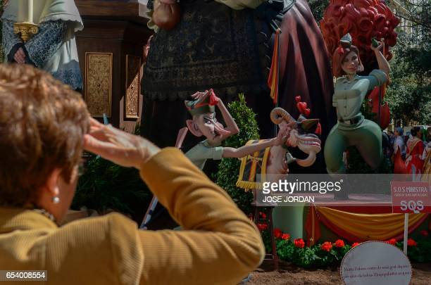 A woman looks at a ninot representing Spanish Minsiter of Defense Maria de Cospedal during the Fallas Festival in Valencia on March 16 2017 Fallas...