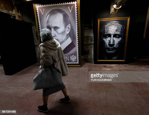 A woman looks at a painting depicting Russian president Vladimir Putin at the 'SUPERPUTIN' exhibition at UMAM museum in Moscow on December 6 2017 /...