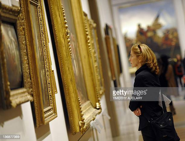 A woman looks at a painting during a Press Preview for the Metropolitan Museum of Art's New American Wing Galleries for Paintings Sculpture and...