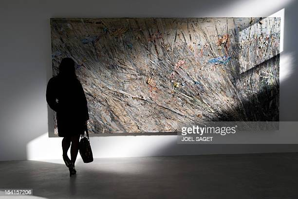 A woman looks at a painting of the serie 'Morgenthau Plan' by German artist Anselm Kieferands exhibited at the art gallery of US art dealer Larry...